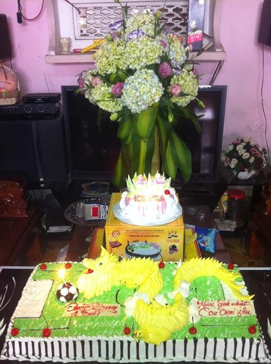 Chiếc bánh sinh nhật lớn hình con rồng tượng trưng cho năm sinh của bé Quốc Long và sân cỏ cùng trái bóng tròn tượng trưng cho niềm đam mê của bố.