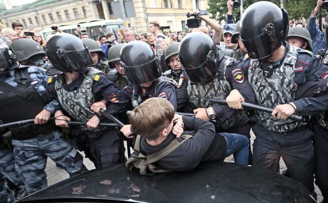 24h qua ảnh: Cảnh sát bao vây cậu bé biểu tình ở Nga