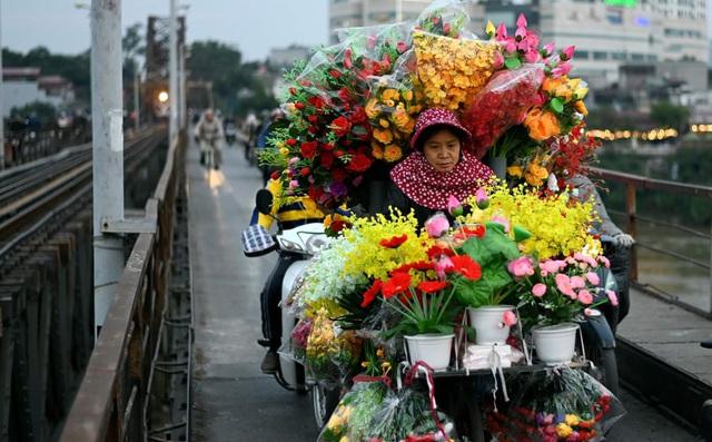 24h qua ảnh: Người bán hoa giả đạp xe trên cầu Long Biên